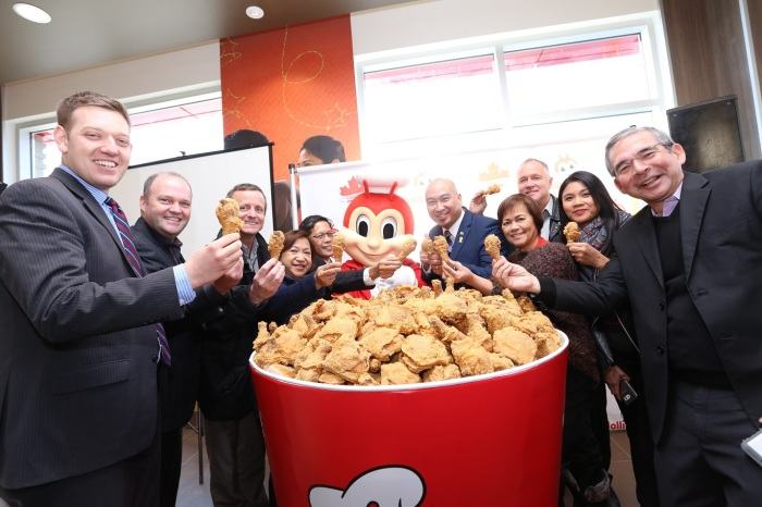 Jollibee executives and special guests gather around a giant bucket of fried chicken for the Jolly Crispy Chicken toast. Seen here are JFC Group President for North America and Foreign Franchise Brands Jose Miñana, VP and General Manager of Jollibee North America Maribeth dela Cruz, Honorary Consul Ronald Opina, Member of the Legislative Assembly for St. Norbert Jon Reyes, President of Sysco Winnipeg Blair Schmidt, Trevor Skinner, and other special guests.