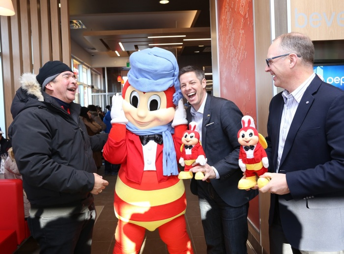 Winnipeg City Mayor Brian Bowman (middle), and City Councilor Scott Gillingham of St. James ward (right) share hearty laughter with Jose Miñana (left) and the Jollibee mascot as they receive exclusive Jollibee dolls to commemorate the occasion.